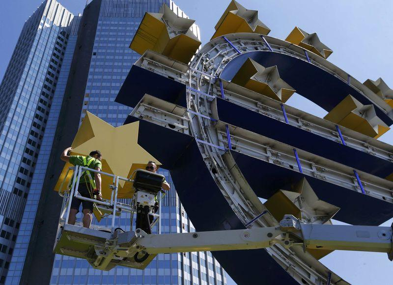 Workers dismantle Euro sign sculpture for maintenance in front of former headquarters of ECB in Frankfurt